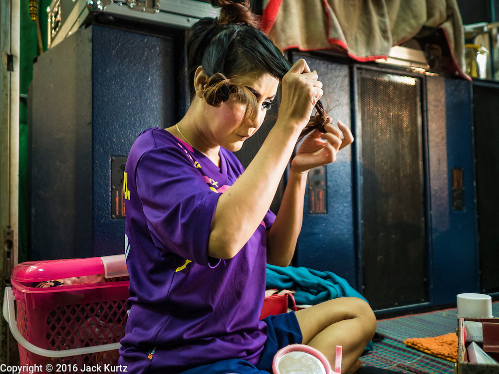 "30 JANUARY 2016 - NONTHABURI, NONTHABURI, THAILAND: A woman fixes her hair before a ""likay"" show at Wat Bua Khwan in Nonthaburi, north of Bangkok. Likay is a form of popular folk theatre that includes exposition, singing and dancing in Thailand. It uses a combination of extravagant costumes and minimally equipped stages. Intentionally vague storylines means performances rely on actors' skills of improvisation. Like better the known Chinese Opera, which it resembles, Likay is performed mostly at temple fairs and privately sponsored events, especially in rural areas. Likay operas are televised and there is a market for bootleg likay videos and live performance of likay is becoming more rare.     PHOTO BY JACK KURTZ"
