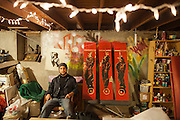 Artist Aron Venegas with his work at a friend's studio in El Paso. He is a founding member of Puro Borde, a cross border group of artists in El Paso, USA, and Ciudad Juarez, Mexico.<br /> <br /> His unfinished panels depict murdered bodies being hung from a bridge in Ciudad Juarez by the killers. Aron happened to drive by the scene that day.<br /> <br /> El Paso, Texas, USA.<br /> <br /> &copy; Stefan Falke<br /> www.stefanfalke.com<br /> LA FRONTERA: Artists along the US Mexican Border