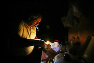 Manuel tries to fix a oil lamp while holding the phone (flashlight) between his teeth.