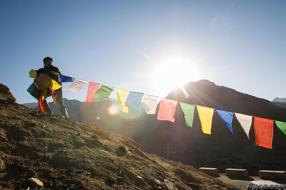 A Tibetan man hangs prayer flags near the Namgyal Tsemo Gompa in Leh, India.