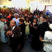 Ray Lampkin joins other members of the Emmanuel Temple Church congregation in prayer at the altar at the end of another Sunday service.  Church was clearly his savior and turned him from a life of drugs into a successful businessman and proud parent.