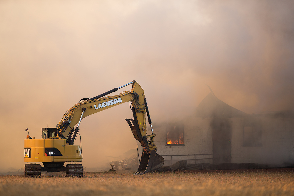 An excavator assists firefighters as they battle a barn fire near St. Thomas, Ont. Monday,  February 1, 2016. About 100 cattle were in the dairy barn when it went up in flames. Only a handful escaped.<br /> Farmers Forum/ Geoff Robins