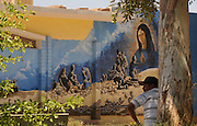 A man in Altar, Sonora, Mexico waits near a mural that depicts the deadly border crossing through the Arizona desert.  The plaza is a known location where others gather to be transported to the U.S. and Mexico border at Arizona, where migrants enter the United States illegally.