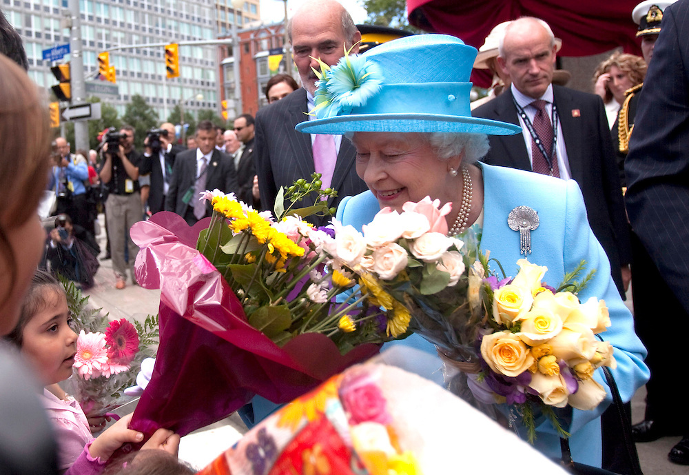 Queen Elizabeth accepts flowers from children during a visit to the National Arts Centre in Ottawa, Canada, June 30, 2010 where she unveiled a statue of Canadian jazz pianist Oscar Peterson. The Queen is on a 9 day visit to Canada. <br /> AFP/GEOFF ROBINS/STR