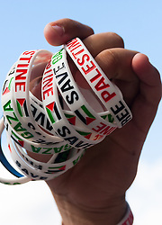 """London, August 23rd 2014. """"Save Palestine"""" bracelets are offered for sale to raise funds as protesters outside Downing Street demand that Britain stops arming Israel."""