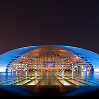 China, Beijing, National Centre for the Performing Arts building, also called The Egg, designed by architect Paul Andreu, glows at dusk on spring evening
