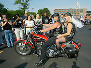 The first couple to be wed at the 100th anniversary celebration for the legendary U.S. motorcycle company Harley-Davidson pulls up outside the company headquarters in Milwaukee August 28, 2003.  Lester Searcy (L), driving a 2002 Harley Low Rider FXDL carries his bride-to-be Mary Ann Tripoli.  Fourteen couples were to be married over the four day celebration.  REUTERS/Rick Wilking