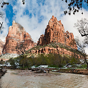 The sandstone cliffs of the Court of the Patriarchs tower over the Virgin River in Zion National Park, near Springdale, Utah, USA. The North Fork of the Virgin River carved spectacular Zion Canyon through reddish and tan-colored Navajo Sandstone up to half a mile (800 m) deep and 15 miles (24 km) long. Uplift associated with the creation of the Colorado Plateaus lifted the region 10,000 feet (3000 m) starting 13 million years ago. Zion and Kolob canyon geology includes 9 formations covering 150 million years of mostly Mesozoic-aged sedimentation, from warm, shallow seas, streams, lakes, vast deserts, and dry near-shore environments. Mormons discovered the canyon in 1858 and settled in the early 1860s. U.S. President Taft declared it Mukuntuweap National Monument in 1909. In 1918, the name changed to Zion (an ancient Hebrew name for Jerusalem), which became a National Park in 1919. The Kolob section (a 1937 National Monument) was added to Zion National Park in 1956. Unusually diverse plants and animals congregate here where the Colorado Plateau, Great Basin, and Mojave Desert meet. (Panorama stitched from 6 photos.)