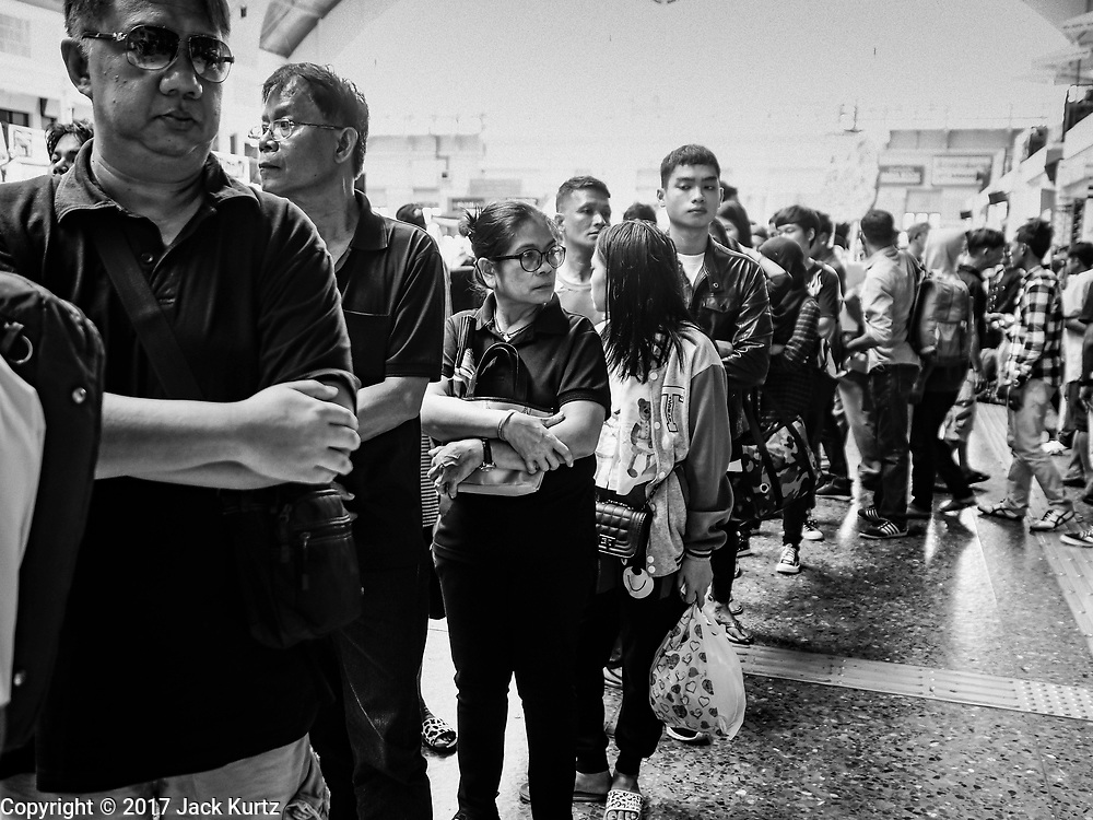 "11 APRIL 2017 - BANGKOK, THAILAND:  Travelers wait in line at the ticket counter in the main waiting room in Hua Lamphong train station during the Songkran travel period at Hua Lamphong train station in Bangkok. Songkran is the traditional Thai Lunar New Year. It is celebrated, under different names, in Thailand, Myanmar, Laos, Cambodia and some parts of Vietnam and China. In most places the holiday is marked by water throwing and water fights and it is sometimes called the ""water festival."" This year's Songkran celebration in Thailand will be more subdued than usual because Thais are still mourning the October 2016 death of their revered Late King, Bhumibol Adulyadej. Songkran is officially a three day holiday, April 13-15, but is frequently celebrated for a full week. Thais start traveling back to their home provinces over the weekend; busses and trains going out of town have been packed.    PHOTO BY JACK KURTZ"