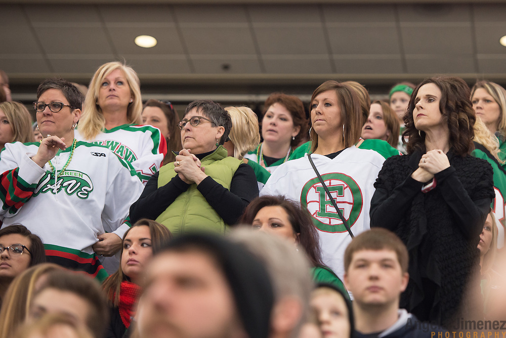 A group of East Grand Forks fans, mostly mothers and sisters of the players, cheer towards the end of the Class A semifinal game between Mahtomedi and East Grand Forks (East Grand Forks won 5-2) at the Minnesota State High School League Boys' State Hockey Tournament at the Xcel Energy Center in St. Paul, Minnesota on March 6, 2015. <br />  <br /> <br /> Photo by Angela Jimenez for Minnesota Public Radio www.angelajimenezphotography.com