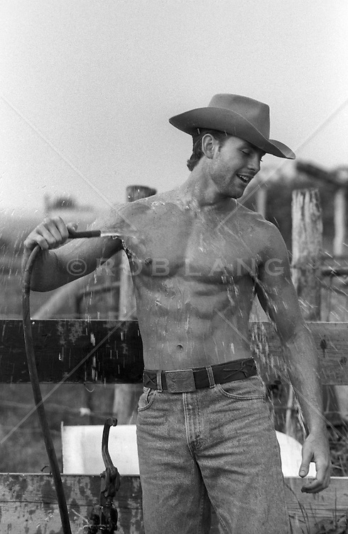 hot cowboy cooling off with water from a garden hose on a ranch