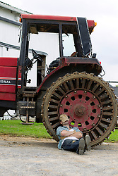 farmer taking a break from work, resting against a tractor tire on a farm