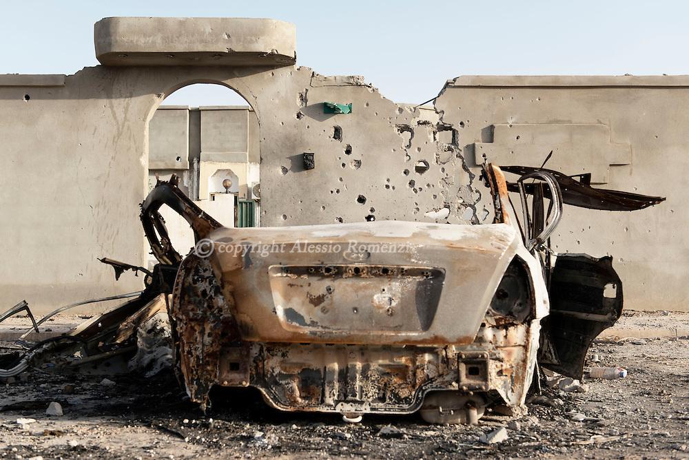 Libya: Riddled by gunshots wall and burned car in 700 neighbourhood in Sirte. Alessio Romenzi