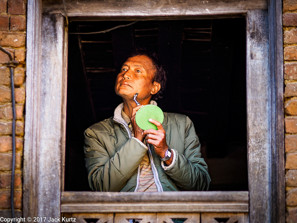 02 MARCH 2017 - SANKHU, NEPAL: A man shaves in the open window of his home in Sankhu. His is one of the few homes in the town not damaged in the 2015 earthquake. There is more construction and rebuilding going on in Sankhu, west of central Kathmandu, than in many other parts of the Kathmandu Valley nearly two years after the earthquake of 25 April 2015 that devastated Nepal. In some villages in the Kathmandu valley workers are working by hand to remove ruble and dig out destroyed buildings. About 9,000 people were killed and another 22,000 injured by the earthquake. The epicenter of the earthquake was east of the Gorka district.   PHOTO BY JACK KURTZ
