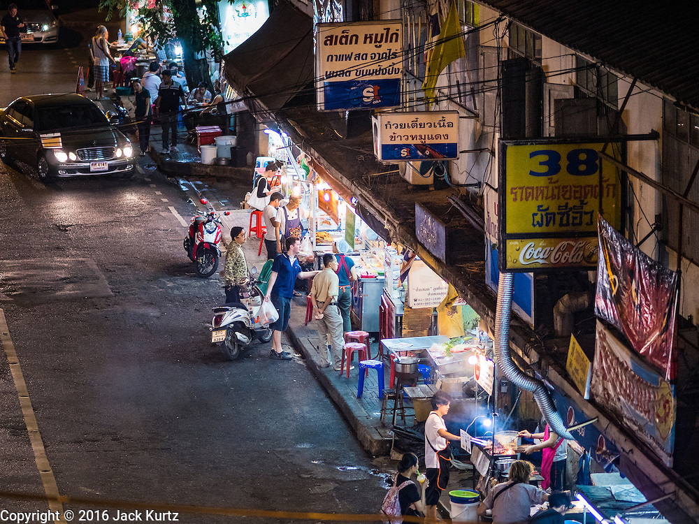 17 JANUARY 2016 - BANGKOK, THAILAND: People on Sukhumvit Soi 38, one of the most famous street food areas in Bangkok. The food carts and small restaurants along the street have been popular with tourists and Thais alike for more than 40 years. The family that owns the land along the soi recently decided to sell to a condominium developer and not renew the restaurant owners' leases. More than 40 restaurants and food carts will have to close. Most of the restaurants on the street closed during the summer of 2015. The remaining restaurants are supposed to close by the end of this week.        PHOTO BY JACK KURTZ