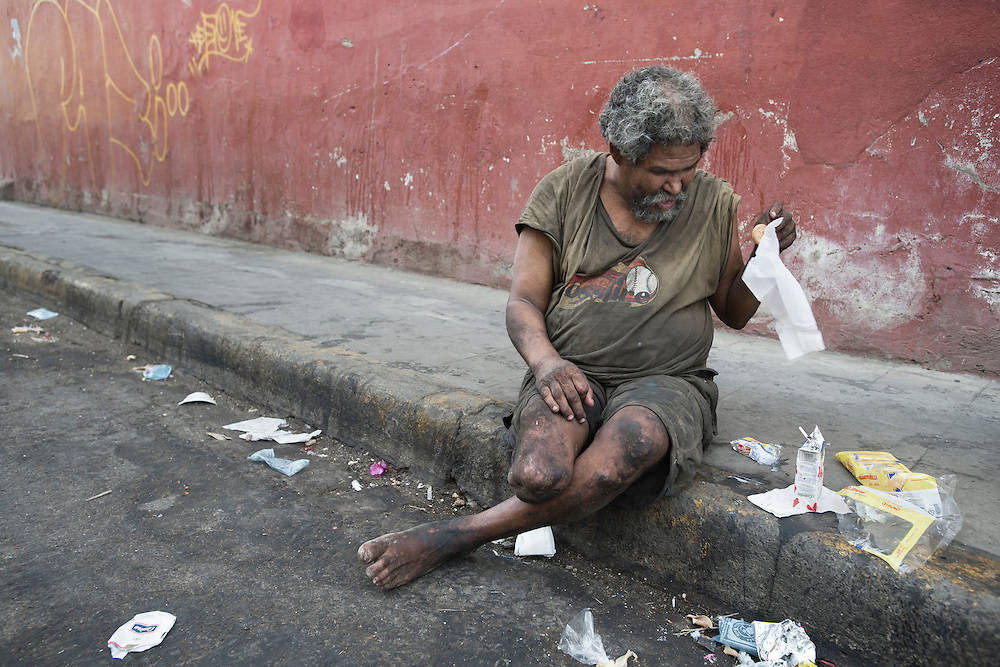 A homeless man who lost a leg eats from the gutter in León, Nicaragua.
