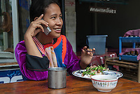 A Lisu woman talks on her cell phone while see sits before a plate of rice, pork and chili's, Northern Thailand