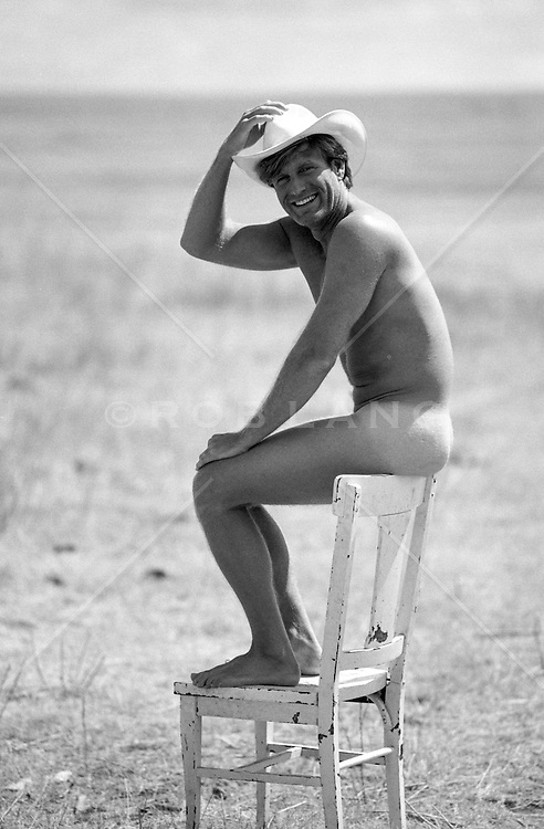 handsome cowboy without clothing sitting on the back of a