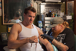 All American man getting a tattoo on his arm by a tattoo artist