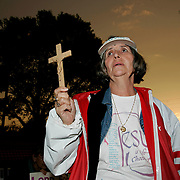 Nancy Hamel holds up a cross while praying for Terri Schiavo as the sun sets outside of the Woodside Hospice on March 23, 2005 in Pinellas Park, Florida. REUTERS/Scott Audette)