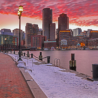 Boston Ablaze featuring winter Boston Harbor skyline photography from New England Photography Guild member and award winning fine art photographer Juergen Roth showing Boston Financial Waterfront District landmarks such as One International Place, Boston Harbor Hotel, Independence Wharf, Department of Homeland Security building, and other structures along Rowes Wharf photographed on a beautiful winter sunset evening. The last light was painting the cloudscape in fire red hues and the long exposure time ensured the intentional blurry cloud movement. <br />