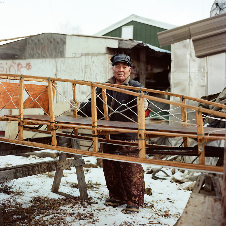 """""""These are my dad's old sleds. The runners are bent, so I am taking it apart to rebuild it. I have been building sleds for quite a while. My dad taught me; he would watch me and when I would make a mistake, he would straighten me out, which was good, you know. He would watch and tell me, """"you're not doing it right, right there"""" and either I would take it apart or just keep on building. I would try not to get mad. Then I had to do it right, which is good. The airfare is getting pretty high here and the gas. So, it's better off to get some dogs I think, and a lot cheaper. We have seven of our own kids and we adopted five more girls. We have a big family."""" —Oscar Griest Sr., is Inupiaq from Shungnak, Alaska. He is working on a handmade sled to pull behind his snow machine. Similar types of sleds are used for dog mushing."""