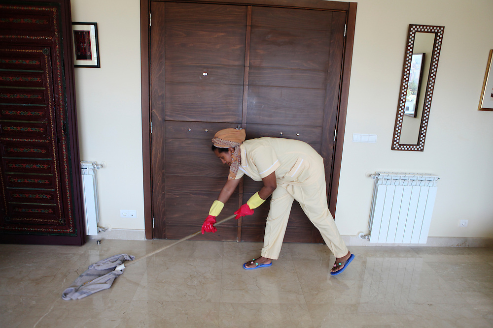 An Ethiopian woman washes the floors of her employer's home.