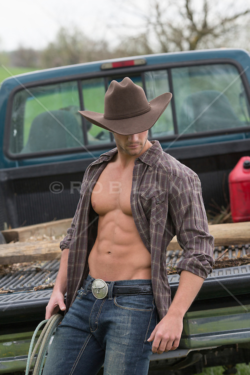 Cowboy With An Open Shirt Leaning On A Truck