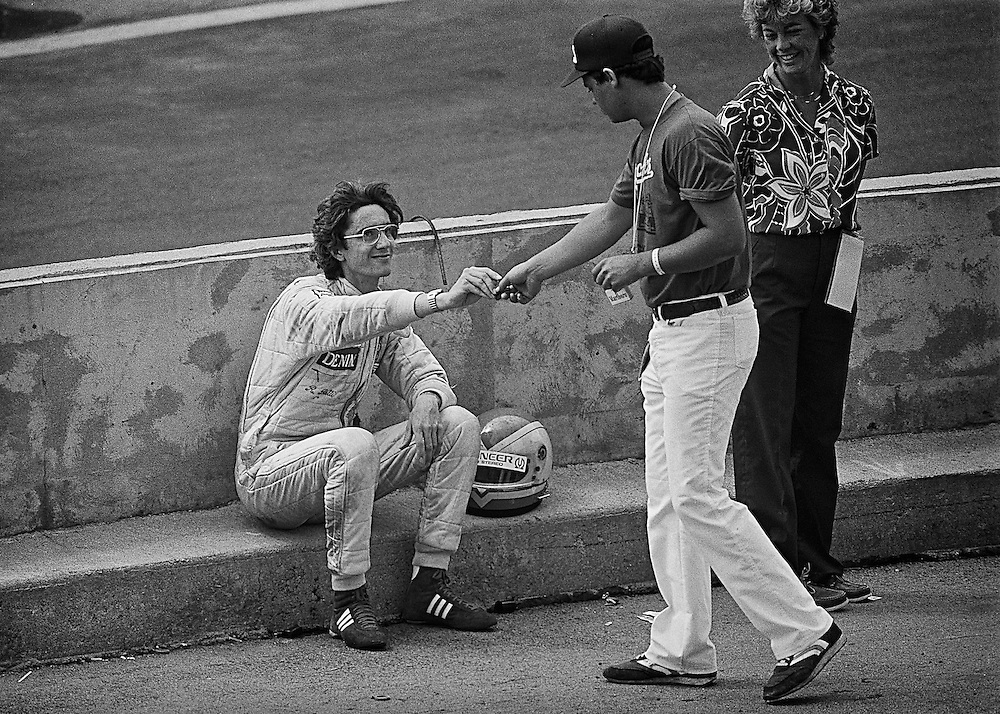 Italian Formula 1 Rookie Riccardo Paletti crashed in his  Osella when the right rear drive shaft broke over a bump during practice for the 1982 Detroit Grand Prix. <br /> <br /> The car was destroyed, but he would walk away unscathed. Here he is offered a cigarette by a corner safety worker. <br /> <br /> Tragically, he would be killed a week later at the start of the Canadian Grand Prix. Launching his car from the last row, he would hit the rear of the stationary Ferrari of Didier Pironi stalled on the grid and succumb to his injuries. <br /> <br /> He was never able to complete a single Grand Prix full-grid race lap.