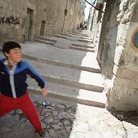 Israel, Jerusalem, Portrait Palestinian boy throwing rock in streets of Arab Quarter