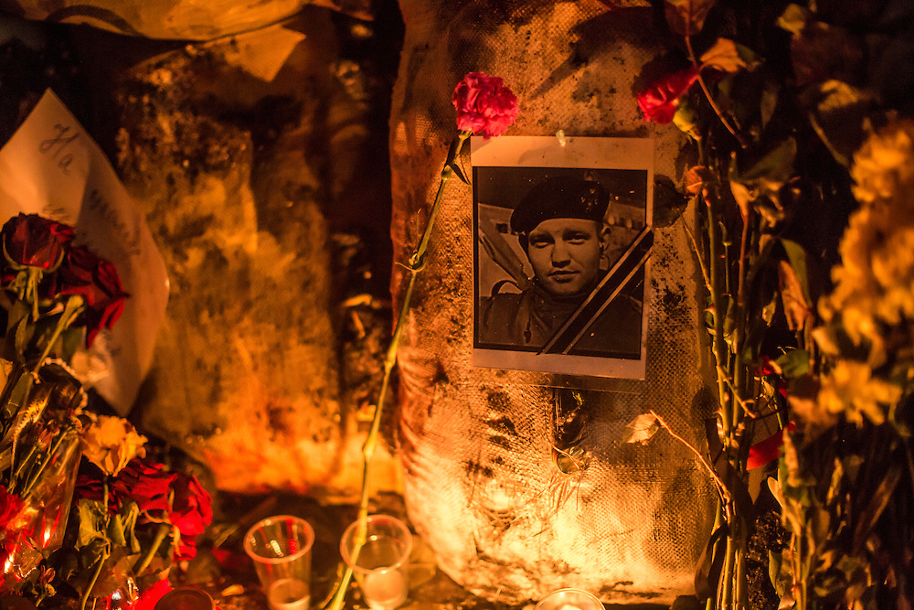 KIEV, UKRAINE - JANUARY 26: Candles burn at a memorial to Mikhail Zhiznevsky, 25, an anti-government protester who was killed in clashes with police, along barricades on Hrushevskoho Street near Dynamo stadium on January 26, 2014 in Kiev, Ukraine. After two months of primarily peaceful anti-government protests in the city center, new laws meant to end the protest movement have sparked violent clashes in recent days. (Photo by Brendan Hoffman/Getty Images) *** Local Caption ***