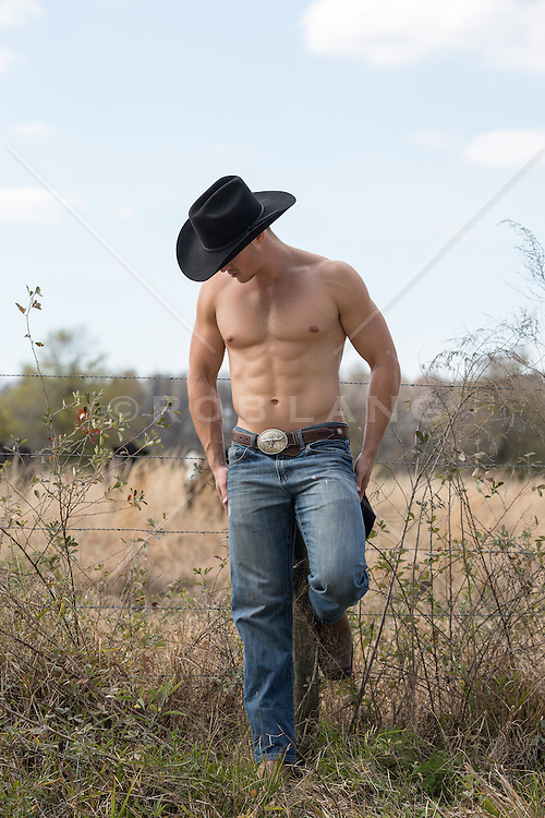 muscular shirtless cowboy on a ranch leaning on a rural fence