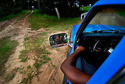 Twenty-one-year-old Brandon Dixon drives a pick-up truck through the dirt streets of Hog Hammock, Thursday, Aug 23, 2012, on Sapelo Island, Ga. The roads in the African Geechee-Gullah community are simple dirt roads without traffic signs, marking or lighting. Property owners are facing higher taxes, and fees from the county tax assessor, threatening an already fragile community. (Stephen Morton for The New York Times)