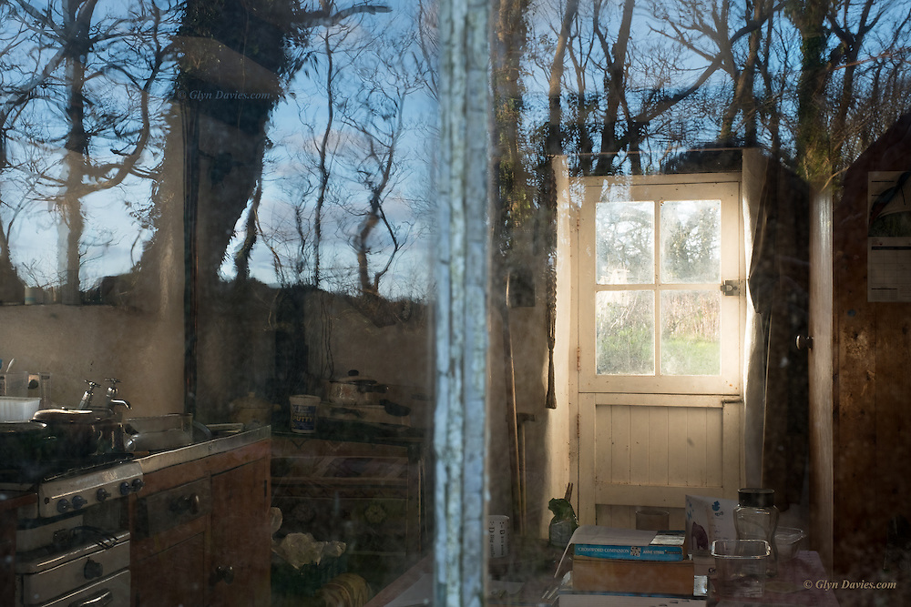 We stumbled across what we thought was a derelict cottage in the middle of woodland down a tiny track. <br /> <br /> Evening sunlight was pouring through a window beyond, and there was a reflection of the sky and trees in the front windows. I went up to the window &amp;  was shocked to discover signs of habitation. There was even a calendar from 2015 on the wall, yet still I suspected that the place had just been deserted. I took this one image because of the beautiful light and sense of time passing, melancholy almost but imbued with such positive afternoon sunshine. <br /> <br /> It was only then that I heard a car pull up behind us. The very jovial driver was the landowner, and he told us that someone does indeed live there. The tenant is a 75 year old man who refuses to connect any power to the house, even though all the faciities are there. He only has a gas bottle to power his ancient stove. <br /> <br /> This old man has a tiny garden plot over a mile away on a steep cliff side, and he walks there regulalrly to tend his vegetagbles. He has an old car, but that is one of his only links wih modern&rsquo;ish technology. <br /> <br /> The landowner is in no hurry to move the old gentleman on, and it seems he will see the end of his days in this ancient farmyard cottage, almost off the grid, and I hope deeply happy because of it. <br /> <br /> Next time I&rsquo;m down, I&rsquo;d love to photograph the old man himself, if he&rsquo;d be happy for me to do so. What a character he must be.