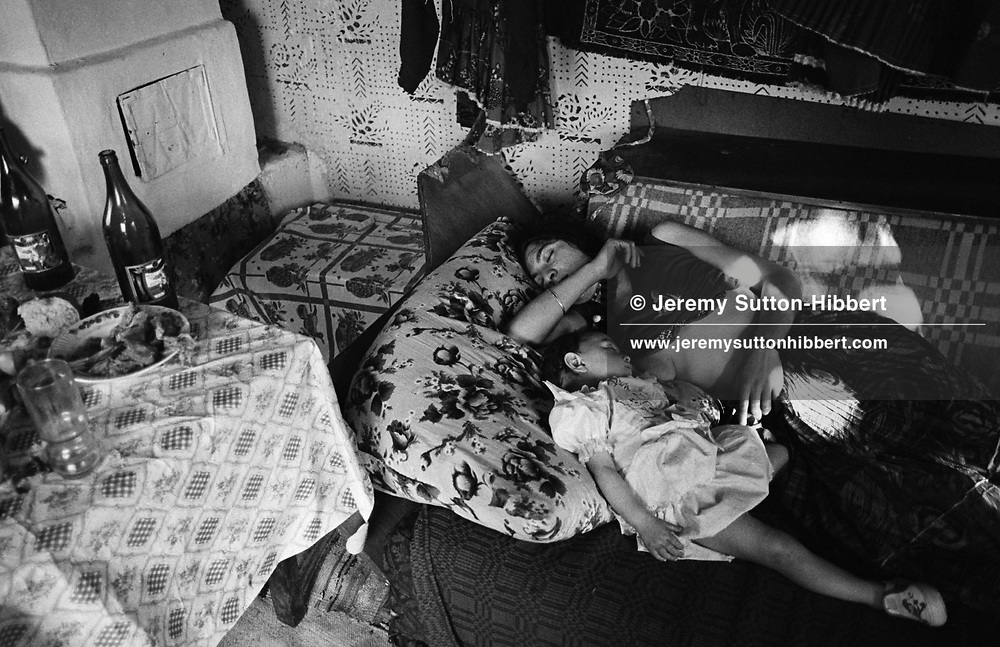 Kalderash Roma Papusha MIhai falls asleep with daughter Garoafa, after breast feeding her. The table has the remains of their meal in celebration of Romanian Orthodox Easter, the most important festivity in the calender for the Roma of Sintesti camp, near Bucharest..