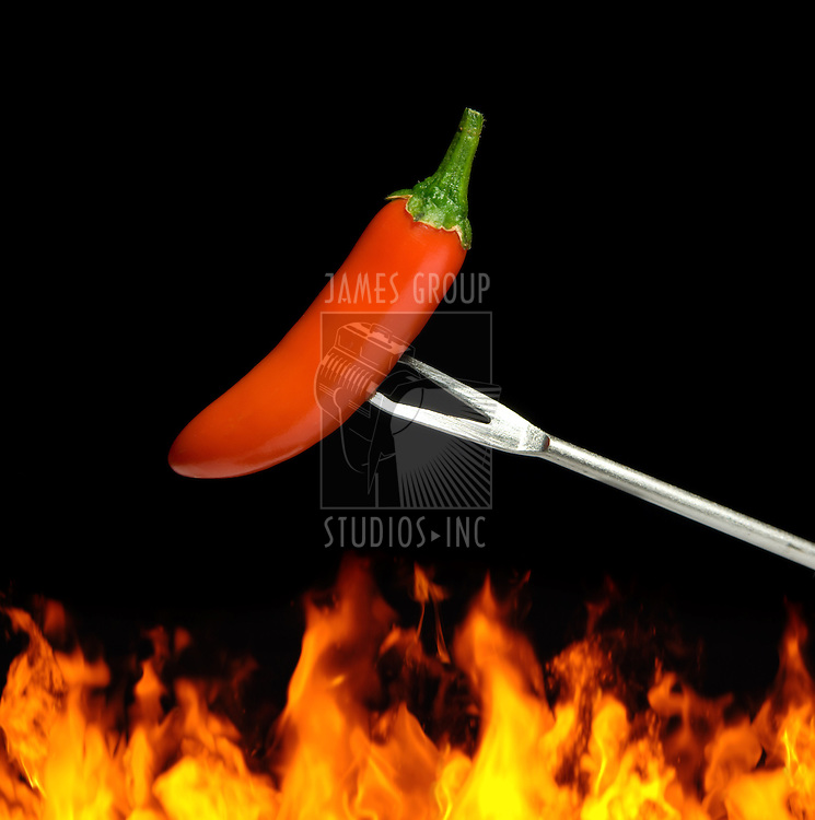 Red chili pepper over flames on a black background