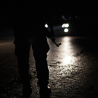 A policeman stands in the dark on a street of nothern Gaza. Un poliziotto nelle strade buie del nord Gaza