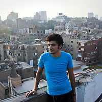 The artist called Ganzeer, aka Mohamed Fahmy, poses for a photograph on a rooftop of a space he used as a studio with other Egyptian artists in Cairo, Egypt. August 2011.