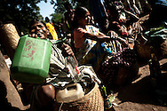 Tribal women sell distilled alcohol at a market in the state of Chhattisgarth in India October 16, 2009. The market is one of the only opportunities where tribal residents of the area can buy and sell good need for survival such as produce, textiles, and other goods in the state where a Maoist movement has brought violence and a disruption of government. The Indian government has begun to increase it's presence of police and military in Naxal dominated states such as Maharastra and Chhattisgarth in response to recent levels of violence by Naxals including an incident where an ambush killed 17 state police.