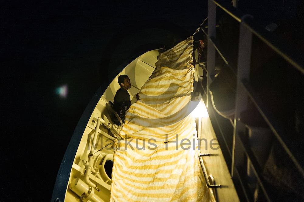 Ein Fluechtling sitzt am 22.09.2016 auf dem Fluechtlingsrettungsboot Sea-Watch 2 in internationalen Gewaessern vor der libyschen Kueste auf dem Verdeck. Foto: Markus Heine / heineimaging<br /> <br /> ------------------------------<br /> <br /> Veroeffentlichung nur mit Fotografennennung, sowie gegen Honorar und Belegexemplar.<br /> <br /> Publication only with photographers nomination and against payment and specimen copy.<br /> <br /> Bankverbindung:<br /> IBAN: DE65660908000004437497<br /> BIC CODE: GENODE61BBB<br /> Badische Beamten Bank Karlsruhe<br /> <br /> USt-IdNr: DE291853306<br /> <br /> Please note:<br /> All rights reserved! Don't publish without copyright!<br /> <br /> Stand: 09.2016<br /> <br /> ------------------------------