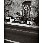 """SHOT 1/30/10 5:14:08 PM - The Virgin Mary painted on rock along Highway 15 near Coyotitian, Mexico. The Virgin of Guadalupe has symbolized the Mexican nation since Mexico's War of Independence. Our Lady of Guadalupe (Spanish: Nuestra Señora de Guadalupe) is a celebrated Catholic icon of the Virgin Mary also known as the Virgin of Guadalupe (Spanish: Virgen de Guadalupe). The Lady of Guadalupe is of significant importance to Mexican Catholics and has been given the titles of """"Queen of Mexico"""", """"Empress of the Americas"""", and """"Patroness of the Americas"""". Roadside capillas, or tiny chapels, in the Mexican states of Nayarit, Sinaloa and Sonora. The capillas are common along the roads and highways of Mexico which is heavily Catholic and are often dedicated to certain patron saints or to the memory of a loved one that has passed away. Often times they contain prayer candles, pictures, personal artifacts or notes. (Photo by Marc Piscotty / © 2010)"""