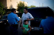 "At left, officer Alberto Cortez Jr. speaks with a family that claims they were threatened by a subject claiming to be affiliated with the Mexican criminal organization ""Los Zetas"" after an argument on August 19, 2010 in Laredo, Texas. The officers at the scene said in recent months there has been an increase in similar claims."