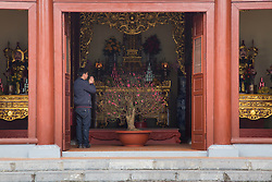 A man prays by an altar of Phu Tay Ho Pagoda during Tet in Hanoi, Vietnam, Southeast Asia