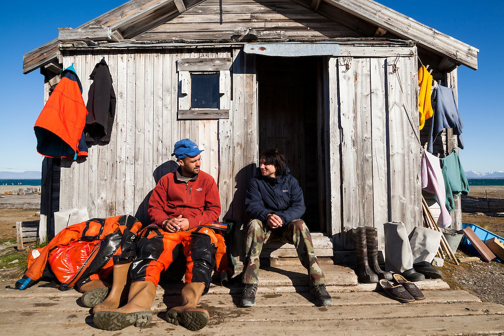 Marcin Tukalski, student at the University of Silesia (right) sits down with geologist Grzegorz Gajek outside the main barracks building in Calypsobyen, Svalbard. Site of a coal mining operation erected by the British Northern Exploration Company in the early 1900s, the structures are now used as a summer field station by Polish researchers.