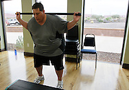 """Guest Greg Dybisz does squats during """"total toning"""" class at the Biggest Loser Resort in Ivins, Utah September 7, 2010.  Guests at the resort affiliated with the popular reality television show, some staying for months, workout in an aerobics room, a gym and a swimming pool for 6 to 7 hours each day and are restricted to a daily 1,200 calorie alcohol and caffiene free diet.  REUTERS/Rick Wilking (UNITED STATES)"""