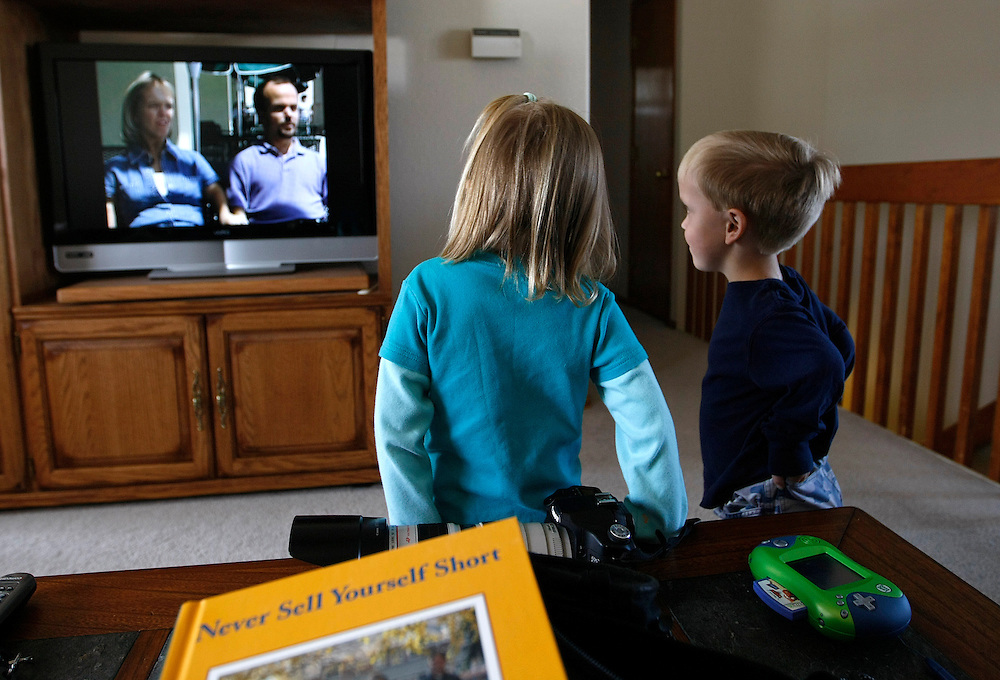 Avery Kotzian, 4 (L) and brother Adam, 6 (R) watch a documentary on Little People featuring their parents Barb (L on screen) and Chris (R on screen) with a book on the topic sitting on the table at their home in Thornton, Colorado March 25, 2010.  Barb, Chris and Adam are achondroplasia dwarfs, a rare genetic disorder of bone growth but daughter Avery is average sized.  Preferring to be called little persons Barb is active in the Little People of America, the only dwarfism support organization that includes all 200+ forms of dwarfism.  REUTERS/Rick Wilking (UNITED STATES)