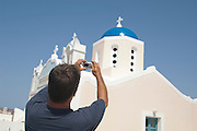 man photographing a beautiful greek church in Santorini, Greece