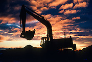Alaska. Silhouette of a excavator at sunset.