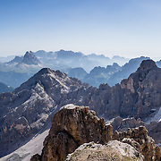 """From Rifugio Guido Lorenzi on Monte Cristallo in the Ampezzo Dolomites, look northeast across blue ridges of the Sesto Dolomites (Dolomiti di Sesto, or Sexten/Sextner/Sextener Dolomiten) towards the pyramids of Tre Cime di Lavaredo (Italian for """"Three Peaks of Lavaredo,"""" called Drei Zinnen or """"Three Merlons"""" in German). A lift to Forcella Staunies on Monte Cristallo gives unforgettable views over the Dolomites mountains (part of the Southern Limestone Alps) near Cortina d'Ampezzo, in the Province of Belluno, Veneto region, Italy, Europe. Monte Cristallo lies within Parco Naturale delle Dolomiti d'Ampezzo. Directions: From Cortina, drive 6km east on SR48 to the large parking lot for Ski Area Faloria Cristallo Mietres (just west of Passo Tre Croci Federavecchia). Take a chair-lift from Rio Gere to Son Forca (rising from 1698m to 2215m). Then take the old style ovovia (egg-shaped) Gondellift Forcella Staunies to Rifugio Guido Lorenzi (2932m) for astounding views. Climbers enjoy spectacular via ferrata routes here. Cortina gained worldwide fame after hosting the 1956 Winter Olympics. UNESCO honored the Dolomites as a natural World Heritage Site in 2009. This panorama was stitched from 2 overlapping photos."""