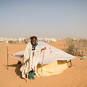 Attaye Ag Mohamed, an elderly refugee living alone, pictured on 11 March 2013 beside the small shelter in which he lives at the Mbera camp for Malian refugees in Mauritania. His refugee card shows that he was registered at the camp on 26 November 2012, but 15 weeks later he has still not received a tent in which to live. Unable to fend for himself, he is fortunate that his neighbours are kindly and look after him - they say he receives no support from NGOs in the camp.